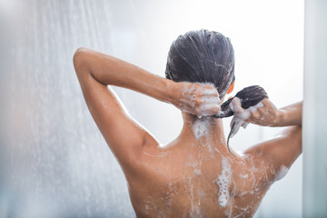 Lady washing hair while relaxing under stream of water. She gesticulating hands