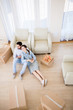 Young restful couple relaxing on the floor of room with three armchairs and several packed boxes