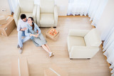 Young relaxed couple sitting on the floor by armchair, having rest and talking after lunch