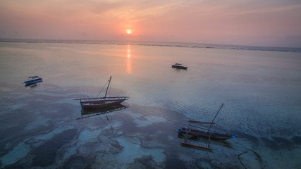 Sunset with fishing boats on blue tropical ocean with drone