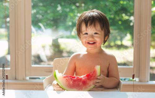 Foto Murales Happy toddler boy eating watermelon in his highchair