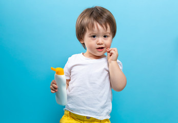 Toddler boy with a bottle of sunblock on a blue background