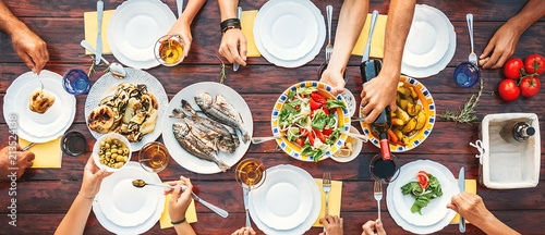 Big family dinner. Top vertical view on the table with dishes and hands - 213524138