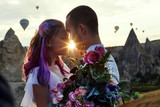 Couple in love stands on background of balloons in Cappadocia. Man and a woman on hill look at a large number of flying balloons. Turkey Cappadocia fairytale scenery of mountains. Wedding on nature