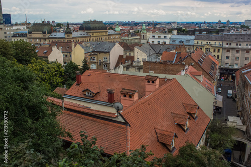 Poster old medieval city roofs of many small buildings from above in evening time