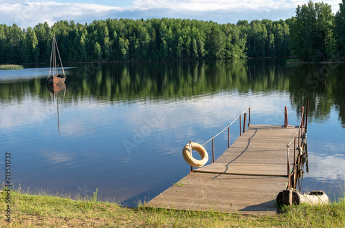 Aluminium Pier A jetty and fishing boat on a forest lake in summer. Photo taken at the Paunküla Reservoir in Estonia
