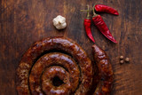 Grilled ring of homemade sausage is on a wooden board with pepper and garlic