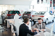 Bearded young male customer signing a contract for rent a car while sitting at car showroom