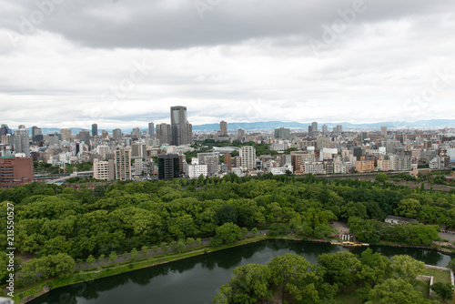 Aerial view of moat around castle park, Osaka business district and spectacular mountains surrounding the city from Osaka Castle.