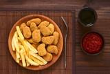 Frische knusprige frittierte und panierte Chicken- oder Hähnchen-Nuggets mit hausgemachten Pommes Frites, fotografiert mit natürlichem Licht - 213555133