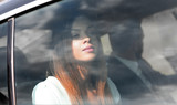beautiful business brunette looks out the window in the car. - 213555395