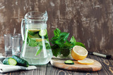 Water detox with lemon, mint  and cucumber  on  wooden background.