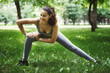 Cute Young woman doing yoga exercises in a green park.