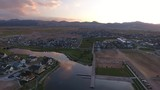 Aerial drone shot of neighborhood community lake with beautiful mountains in backdrop, taken at sunset. - 213568125