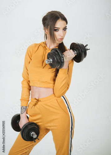 Wall mural gym. woman training in gym. gym sport training. fitness gym with sexy woman holding barbells. dedicated to fitness.