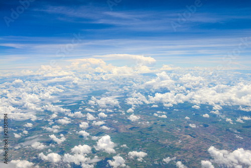 Beautiful view of blue sky above the white clouds and land background from airplane window - 213581194