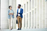 Happy excited office colleagues in stylish outfits talking about work when walking over street in summer - 213584553