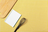 Blank sheet of opened notepad and kitchen utensils on  table with tablecloth, copy space - 213591132
