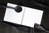 Blank sheet of opened notepad and kitchen utensils on  table with tablecloth, copy space - 213591164