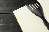 Blank sheet of opened notepad and kitchen utensils on  table with tablecloth, copy space - 213591182