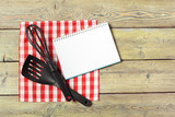 Blank sheet of opened notepad and kitchen utensils on  table with tablecloth, copy space - 213591313