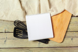 Blank sheet of opened notepad and kitchen utensils on  table with tablecloth, copy space - 213591328