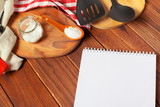 Blank sheet of opened notepad and kitchen utensils on  table with tablecloth, copy space - 213591378