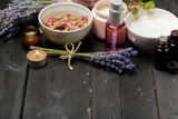 Fototapety Aromatic composition of lavender, herbs, cosmetics and salt on a dark table top