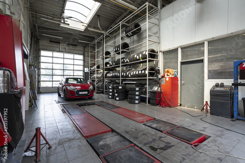 Wall mural Red car in a workshop with tires. Professional vehicle repair