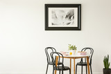 Real photo of a laid dining table with black chairs and painting on an empty wall. Place your graphic - 213599521