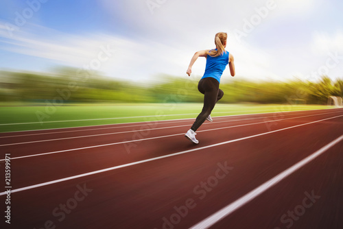 Leinwanddruck Bild beautiful young female athlete running on running track back view on blur background. An athlete runs around the stadium jumping photo in flight. Athletics