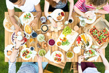High angle of a group of people sitting around a wooden table talking, toasting with colorful drinks and eating vegetarian food - 213602581