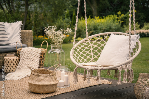 Foto Murales Pillow on hanging chair and basket on carpet in the garden during spring