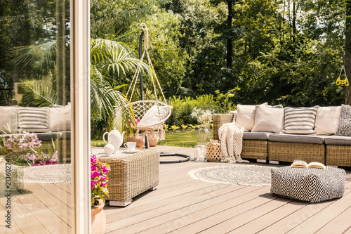 Pouf and rattan sofa on wooden patio with hanging chair in the garden. Real photo © Photographee.eu