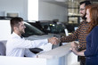 Car dealer and buyer shaking hands after transaction in luxury dealing salon