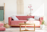 Wooden table in front of red sofa in pastel living room interior with flowers and blanket. Real photo