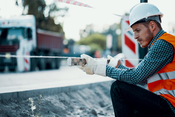 Worker measuring land with a leveling rod at a construction site