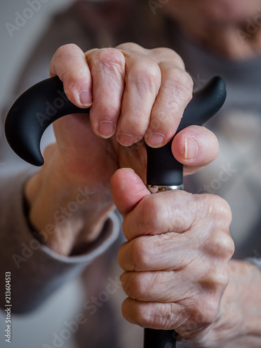 Alte Frau hält einen Stock in der Hand