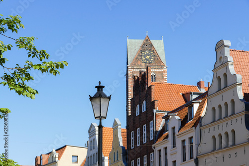 Wismar, houses facades, street lantern and in the background St. Mary's Church