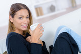 young woman sitting holding a cup of hot beverage - 213610599