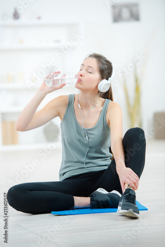 Fotobehang Fitness young athletic woman is drinking water after training