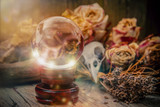 Crystal orb in front of dryed roses and a ravenskull-magic scene - 213612992