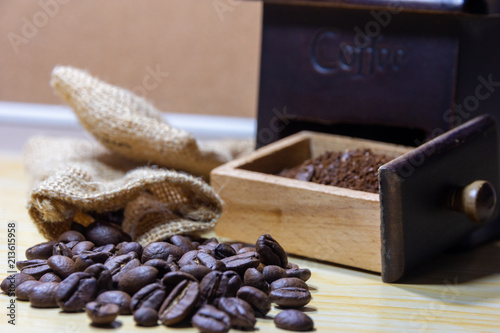 Selective focus coffee beans and grinded beans in vintage wooden coffee grinder and sackcloth on wooden background