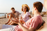 Friends have a rest outdoors on the beach drinking beer. - 213618768