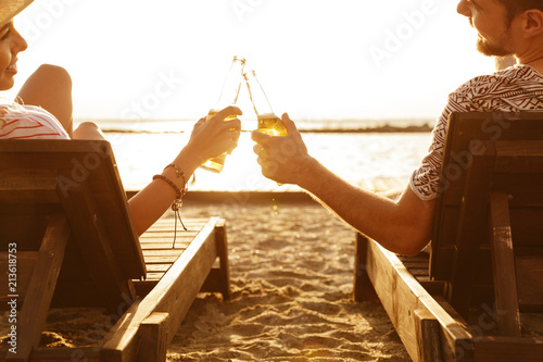Foto Murales Loving couple have a rest outdoors on the beach drinking beer.