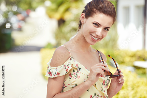 Foto Murales Cute smiling young woman with sunglasses. Holiday time. Sunny day.