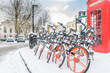 London street in the snow with red telephone box & cycles - 213620951