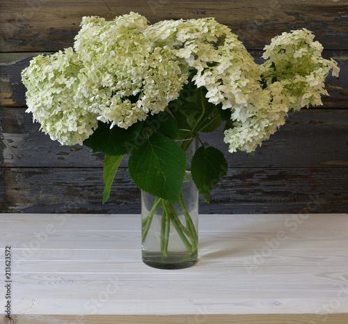 still life with white hydrangea on a vintage wooden background of white and gray