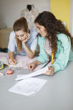 Two pretty designers dreamily drawing sketches of clothes together in sewing workshop - 213629774
