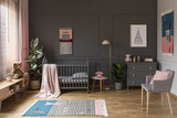 Real photo of a grey crib standing next to a pink stool, a lamp and cupboard in grey baby room interior also with armchair, rug and posters - 213638367